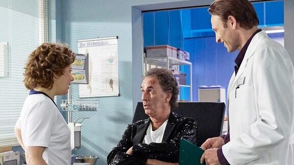Ein älterer Mann sitzt auf einer Liege. Neben ihm stehen ein Arzt und eine Krankenschwester.