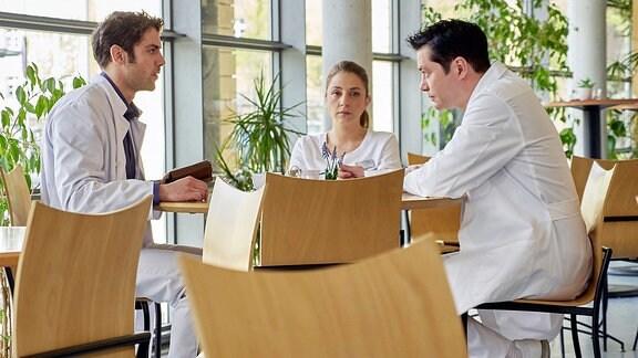Eine Krankenschwester und zwei Ärzte sitzen an einem Tisch.