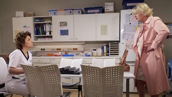 Eine Krankenschwester sitzt an einem Tisch. Vor ihr steht eine Frau, die Hände in die Hüften gestemmt.