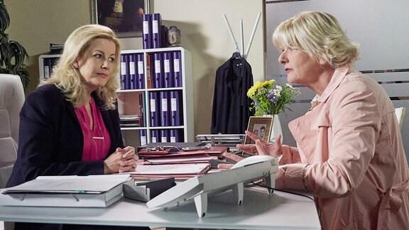 Zwei Frauen sitzen sich einem Schreibtisch gegenüber.