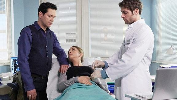 Eine Frau liegt auf einer Krankhausliege. Sie blickt den Mann neben ihr an, während ein Arzt sie behandelt.