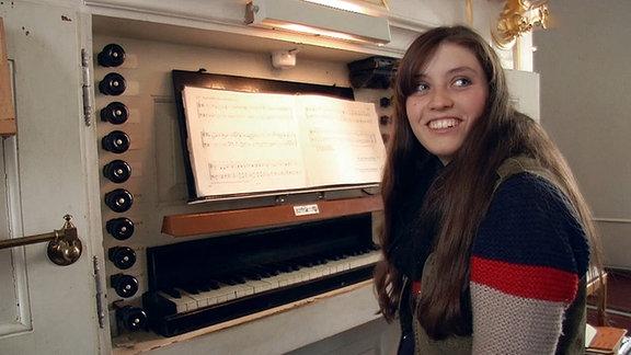 Eine junge Frau sitzt an einer Orgel