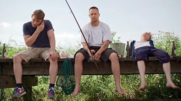 Fuchser, Balla und Jojo sitzen nebeneinander auf einer Brücke. Balla angelt.