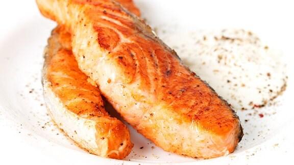 Zwei gebratene Lachsfilets liegen auf einem weißem Teller.