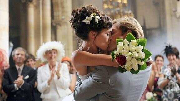 Chloé und Stephen küssen sich auf ihrer Hochzeit.