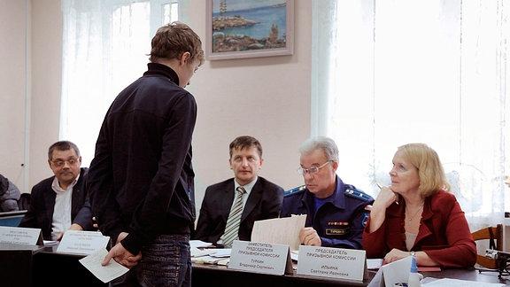 Ein junger Kriegsdienstverweigerer steht vor der Kommission.