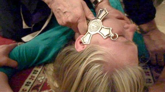 Eine Frau liegt auf dem Boden. Ihr wird ein Kreuz auf das Gesicht gehalten.