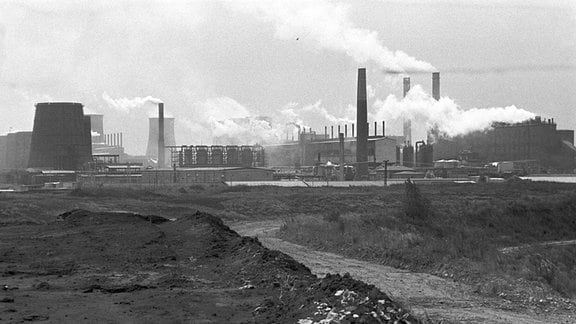 Aus den Schloten des Braunkohleveredlungswerkes Espenhain ziehen ätzende Staubwolken und Gasgerüche über das angrenzende Dorf Mölbis, aufgenommen im Sommer 1990