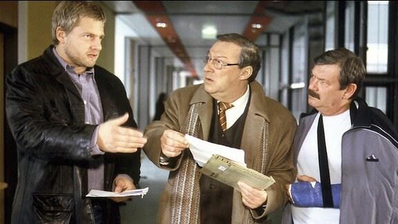 Die Kommissare Schmücke (Jaecki Schwarz, Mitte) und Schneider (Wolfgang Winkler, rechts) unterhalten sich mit einem Mann. Schmücke hält mehrere Akten in der Hand, Schneider trägt an einem Arm einen Gipsverband