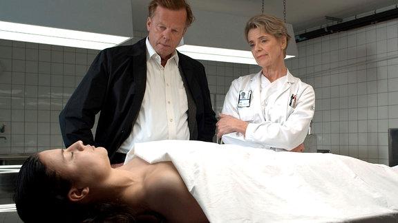 Die Gerichtsmedizinerin Ann-Britt Höglund (Angela Kovacs, rechts) klärt Wallander (Krister Henriksson) über die Todesursache der jungen Therese (Josefine Tengblad) auf