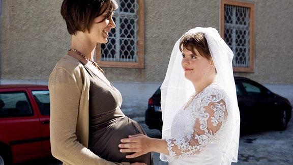 Michalina befühlt den Bauch einer Schwangeren.
