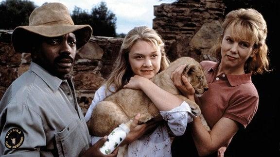Wildhüter George Luello (John Matshikiza; r:), Val (Ariana Richards, M.) und ihre Mutter, die Ärztin Eleanor Porter (Linda Purl), ziehen gemeinsam die verwaiste Löwin Elsa auf.