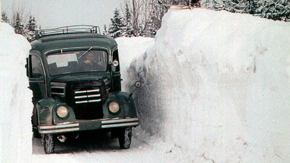 1964, ein Auto fährt auf einer Straße in Oberwiesenthal, Schnee türmt sich rechts und links auf über 2 Meter auf.