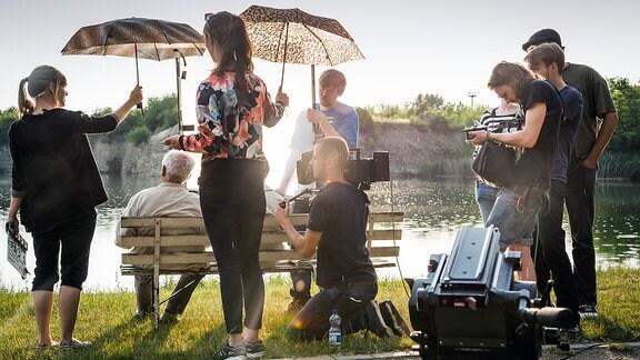 Am See während der Dreharbeiten. Wenn es regnet und gleichzeitig die Sonne blendet ist der Einsatz des ganzen Teams gefragt:Das Team von links: Regie-¬Assistentin (Clara Trischler), Rolle Helmut (Dietmar Obst), Producerin (Julia Klett), Kameramann (Michael Terhorst), 1. Kamera-¬Assistent (Lasse Frobese), Script/Continuity (Yara Behrens), 2. Kamera-¬Assistent (Philip Henze), Regisseur (Clemens Beier), DIT (Robin Paralkar).