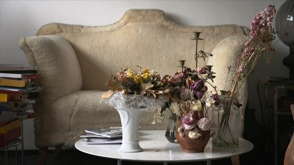Ein Sofa, dovor ein kleiner Tisch mit Vasen in denen sich vetrocknete und verwelkte Blumen befinden.
