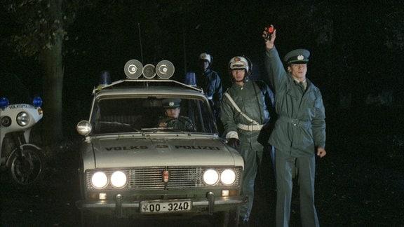 """Die Volkspolizei im Einsatz bei einer nächtlichen Verkehrskontrolle - Polizeiwagen Modell """"Lada"""""""