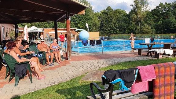 """Ums Freibad kümmern sich die """"Wasserfreunde Reumtengrün"""", der zweitstärkste Verein im Dorf. Die Stammgäste sind eine Gruppe von 13 Rentnern, die von mittags bis abends gemeinsam schwimmen, essen und lachen."""