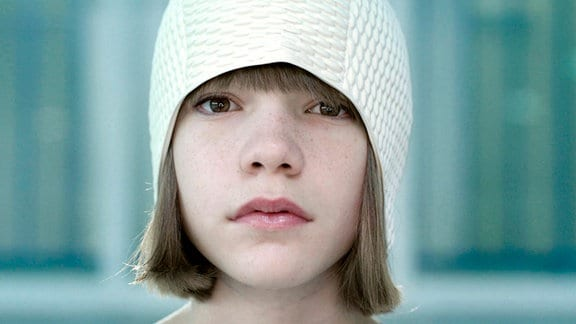 Ein Mädchen mit Bob hat eine Badekappe auf, die Haare hängen heraus.
