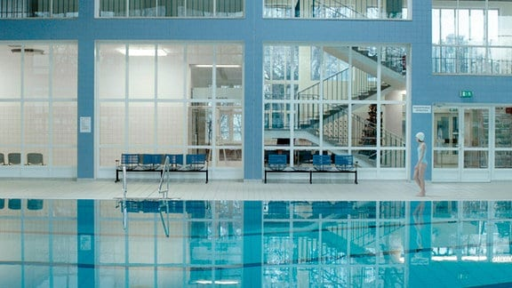Ein Mädchen alleine in einem großen Schwimmbad.