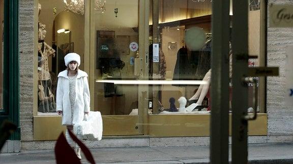 Ein Mädchen steht alleine vor einer großen Eingangstür eines Hauses.