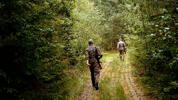 Zwei NVA-Soldaten patrouillieren an der Grenze.