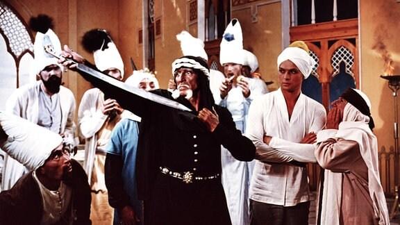 Der böse Zauberer Scham Chur hat ein Schwert auf sich gerichtet und gibt vor, sich selbst töten zu wollen. Hinter ihm stehen Aladins Mutter (E. Werulaschwili), Aladin (Boris Bystrow) und Großwesir (G. Sadychow)