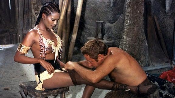 """Roberto (Paolo Villagio) zieht """"Freitag"""" (Zeudi Araya), die auf einem Hocker sitzt, einen Strumpf an."""