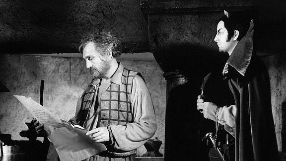 Meister Hans Röckle (Rolf Hoppe, l.) liest einen Vertrag, Mister Flammfuß (Peter Aust) hält eine Feder bereit und sieht Röckle zu.