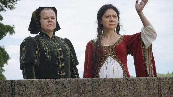Bohdanka und die Königin (Sabina Remundová, l.) schauen in die Ferne, Bohdanka winkt.