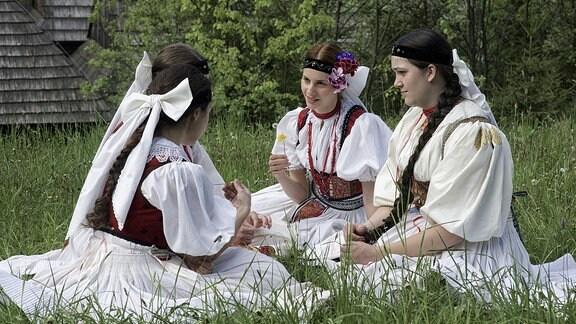 Drei Mädchen in Tracht sitzen auf der Wiese und erzählen sich etwas.