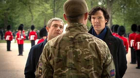 Sherlock (Benedict Cumberbatch, re.) und sein Freund John Watson (Martin Freeman, li.) stehen vor einem Major der Leibgarde der Königin.