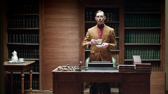 Ein Mann steht mit einer Kaffeetasse in der Hand hinter einem Schreibtisch.
