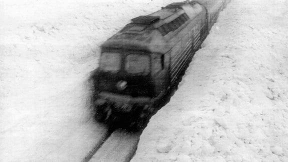 Ein Zug im meterhohen Schnee.