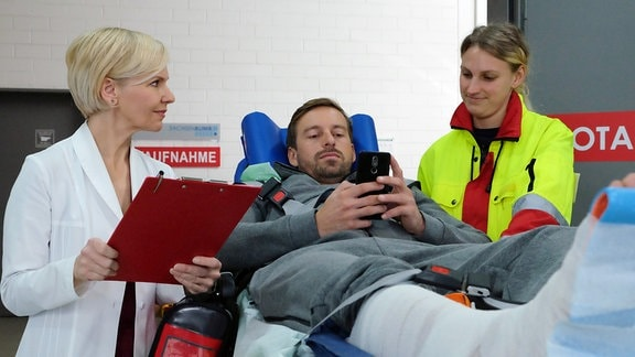 Daniel Kramer (Ben Blaskovic, mi.) wird von der Notärztin (Komparsin, re.) in die Sachsenklinik eingeliefert. Dort übernimmt Dr. Kathrin Globisch (Andrea Kathrin Loewig, li.) den Patienten, der allerdings nur Augen für seine Dating-App hat.
