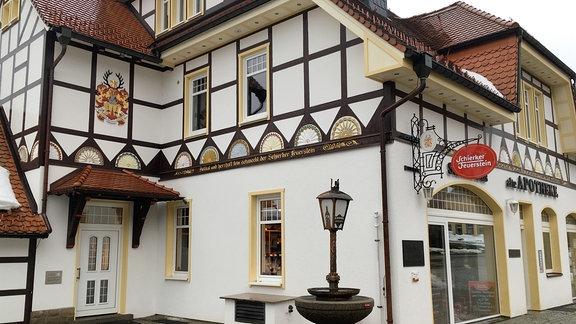 Die Schierker Apotheke ist ein schmuckes Fachwerkhaus in Weiß mit Giebel und  rotem Dach. Davor befindet sich eine historische Straßenlaterne.
