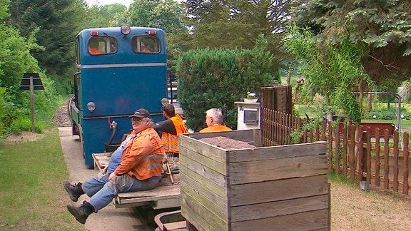 Die Diesellok bringt die Vereinsmitglieder zum Arbeitseinsatz an die Strecke. Natürlich tragen alle ihre Warnwesten, so sind die Vorschriften. Heute werden Gleise mit Schotter unterfüttert. Dafür sind starke Männer gefragt.