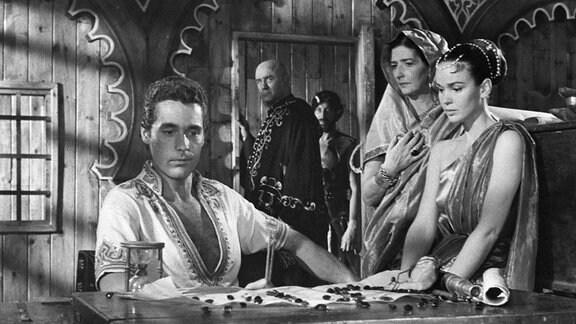 Der böse Zauberer Sokurah (Torin Thatcher, Mitte) bietet Sindbad (Kerwin Mathews, l.) Gold und Edelsteine an, um zurück auf die Insel Colossa zu fahren.