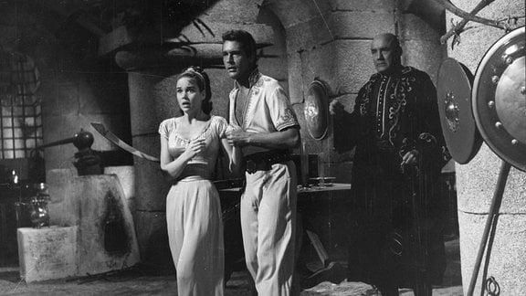 Ein Mann und eine Frau stehen mit erschrockenem Gesichtsausdruck in den Innenräumen einer Burg.