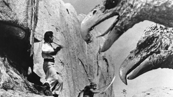 Zwei Männer kämpfen gegen einen riesigen Vogel.