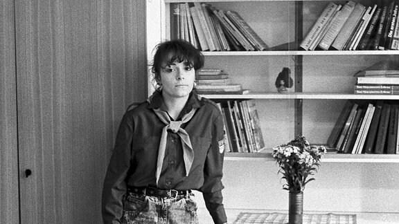 Kandidatin der 1. Leipziger Miss-Wahl, Mai 1989: Ramona March, in einem FDJ-Hemd und mit Halstuch eines Pionierleiters vor einer Anbauwand stehend.