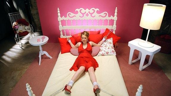 Die 15-jährige Leipzigerin Anna (Lotte Flack) liegt auf einem Bett - gefesselt und ein auffällig rote Kleid tragend.