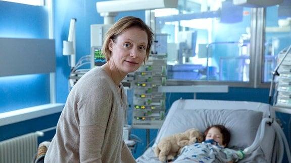 Esther Baumann (Katharina Schubert) am Bett ihres Sohnes Hannes Baumann (Mikke Rasch). Ein angebliches Zucken seines Fuß lässt sie wieder hoffen.