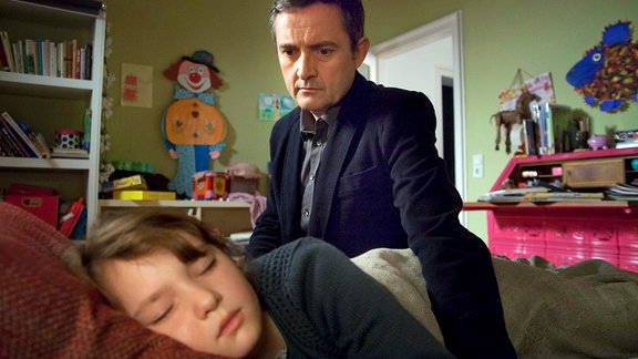 Roman (Harald Schrott) bringt Merle (Greta Bohacek) ins Bett.