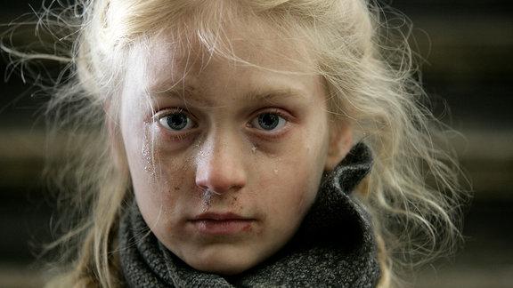 Ein dreckiges und zersaustes Kind schaut in die Kamera.
