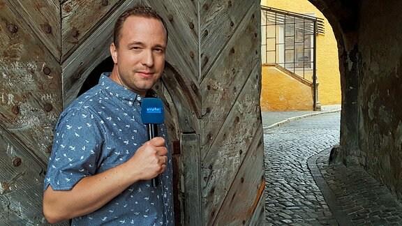 """Mario D. Richardt - Moderator der Sendung """"Mach dich ran!"""", vor dem geöffeneten  Tor eines historischen Gebäudes."""
