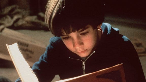 Der kleine Halbwaise Bastian (Barret Oliver), eine passionierte Leseratte, ist in die fesselnde Lektüre eines magischen Buchs vertieft.