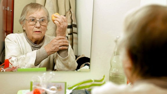 Anneliese (87) blickt in einen Spiegel. In der erhobenen linken Hand hält sie einen Apfel.