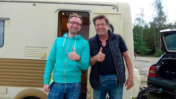 Zwei Männer stehen strahlend vor einem Wohnwagen und halten den Daumen nach oben.