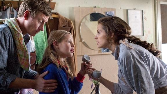 Yvonne Catterfeld (als Katharina)  übergibt einen Telefonhörer an  Flora Li Thiemann (als Friederike, Mitte)-. Links strehend: Maxim Mehmet (als Torsten).