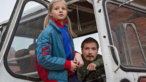 Flora Li Thiemann (als Friederike) steht in der Tür eines Traktors vom Typ ZT 300. Jacob Matschenz (als Onkel Mike)  sitzt in dem Traktor.